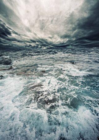 Ocean waves storm clouds horizon gloomy weather .