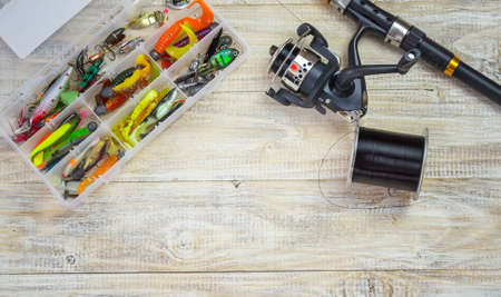 Fishing tackle, many colorful baits with a fishing rod on a wooden pier. Selective focus Banque d'images