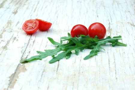 rukola: rocket salad and cherry tomatoes on a grunge table