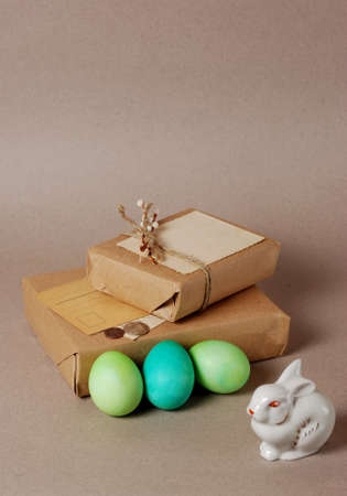 Vintage still life with easter eggs, white bunny and gift boxes in craft paper photo
