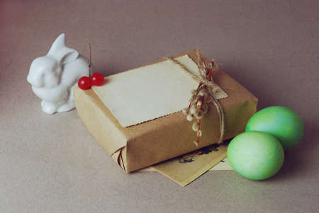 butterflies for decorations: Vintage still life with easter eggs, white bunny and gift boxes in craft paper