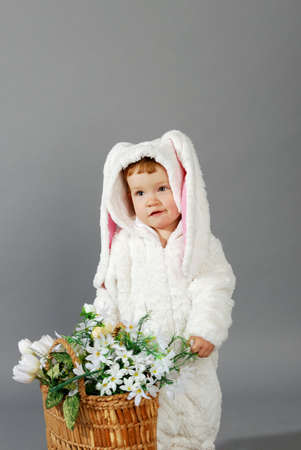 Portrait of a cute little girl dressed in Easter bunny suit holding spring flower bouquet photo