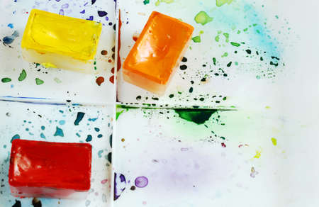 paint box: Tree bright watercolor cases on a paint box with colorful splashes in front of white background