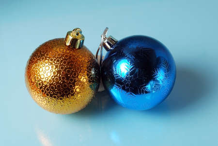 chrom: Golden and blue christmass balls on a blue glass background. Seasonal background