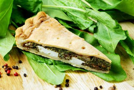 spinach: Empanada de espinacas y queso feta en una mesa de madera con especias y espinacas frescas