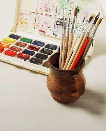 Helle Aquarellfarben und gebrauchte Bürsten für die Malerei. Nahansicht. Standard-Bild - 53297249