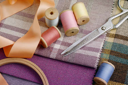 sewing supplies: sewing supplies, needles, scissors on the colorful gunny textile background. Photo in gentle pastel colors