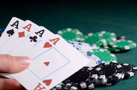 four of a kind: Stack of chips and four of kind poker combination on a green background. Poker game theme