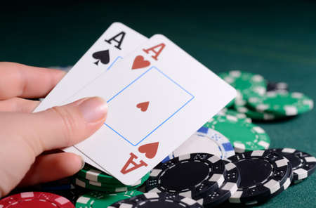 stay in green: Casino chips and pair of aces in a womans hand.