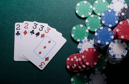 full house: Casino chips and full house cards combination on the green table Stock Photo