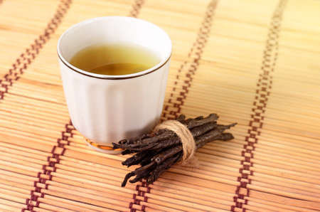 chinese holly: Wellness Tea drink, Bitter Twisted Leaves of Ilex Kudingcha. Green tea Kuding in a white porcelain cup Stock Photo