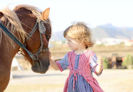 pony girl: Portraiteof a Cute white toddler girl in a rustic style dress caressing brown pony in a field in sunny day Stock Photo