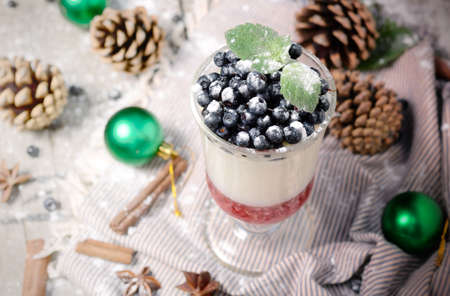 Delicious parfait dessert with bilberry, milk souffle and jello layers. Frozen treat in a glass on rustic wooden background