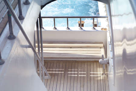 Boat ladder, Deck on the stern of the yacht on a sunny day and beautiful blue sea water.