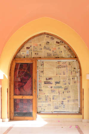 MAKADI, EGYPT - MARCH 21, 2017: Shop doors closed for a while, covered by egyptian newspapers and Nefertiti image in the yard of Jaz Makadi Hotel.