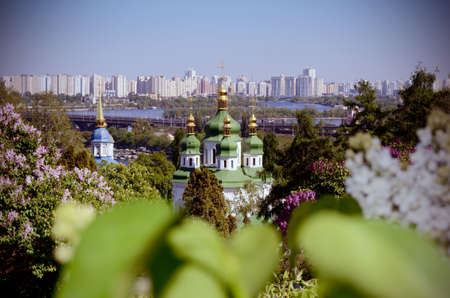 Vydubychi monastery church among lilac bushes in spring. Kiev, Ukraine.