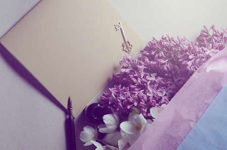 Romantic background with lilac flowers and notebook, sketchbook or diary. Spring season still life
