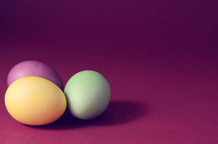 Trendy photo of Three multi colored easter eggs on a dark purple background.