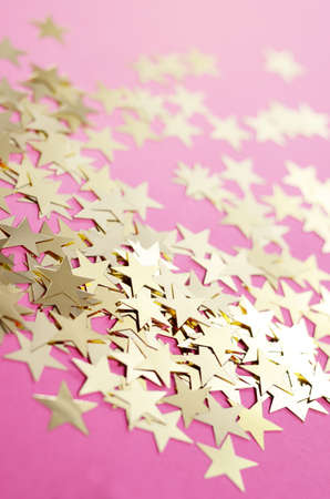 New Year background with sparkling decorative gold stars on a hipster pink background