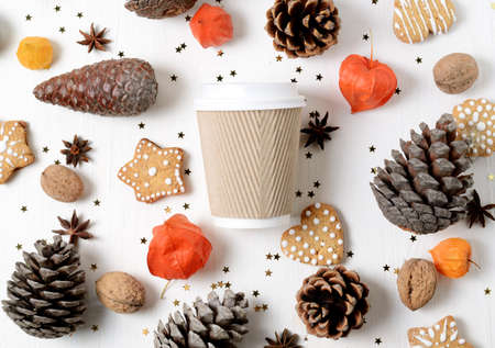 Takeaway paper coffee cup among cookies, pine cones and other christmas decor. Top view trendy photo background Stock Photo