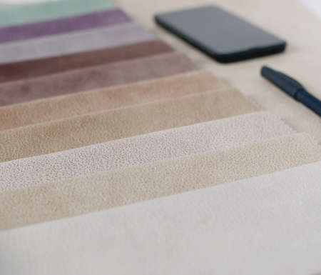 Bright collection of colorful textile samples with suede texture. Mockup with fabric samples, smartphone and black wallet.