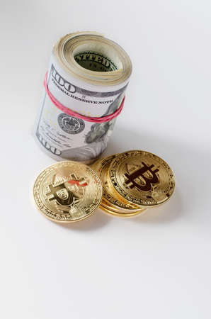 Physical Gold Bitcoin Coin and dollar bill roll on a white background.
