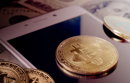 Physical Gold Bitcoin Coin against dollar bills and smartphone on a purple background. Business and financial background Stock Photo
