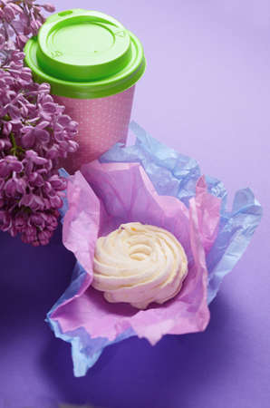 Food Photo of homemade zephyr, marshmallow in violet wrapping paper and coffee to go cup. Sweet dessert on a pink background.