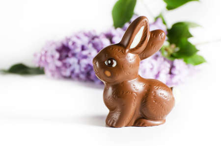Festive still life with Chocolate Easter Bunny and lilac flowers.