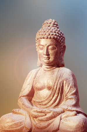 Buddha statue sitting in meditation pose against blurred golden background. Standard-Bild - 115452585