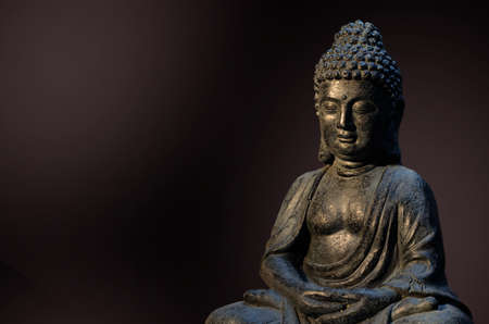 Buddha statue sitting in meditation pose against deep dark background. Stock Photo