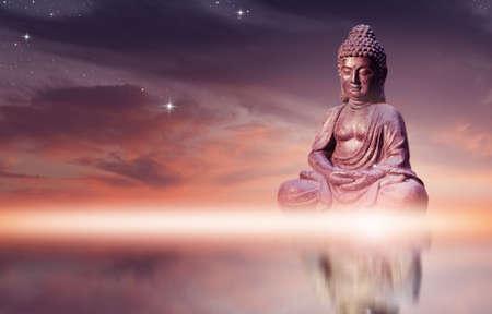Boeddhabeeld zittend in meditatie pose tegen avondrood met gouden tinten wolken.