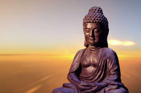 Buddha statue sitting in meditation pose against blurred background.