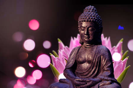 Buddha statue sitting in meditation pose against deep dark background and pink lotus flower behind.