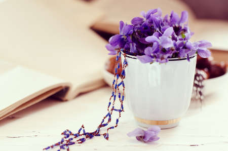 Still life with violet in white cup, old books. Romantic spring floral background.