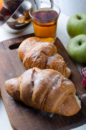 Fresh croissant with tea for breakfast. Food photography background.