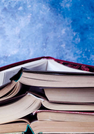 Stack of books piled against blue background. School concept. Imagens
