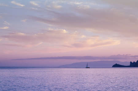 Beautiful pastel toned sunset or sunrise view from the seaside. Yacht on the calm sea surface. Imagens