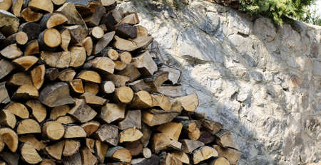 Stack of firewood near stone wall. Natural wooden pattern background. Imagens