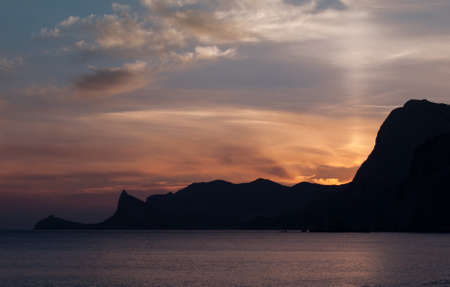 Beautiful bright sunset on the Black Sea in the Sudak. Seaside with outline of cape Kapchik. Crimea landscape.