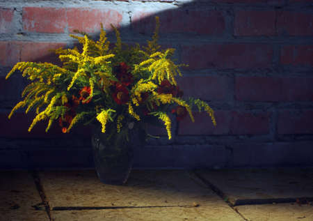 Various autumn flowers bunch against brick wall background.