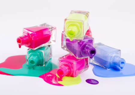 Vibrant Nail polish tubes isolated on white background. Beauty industry concept backdrop.