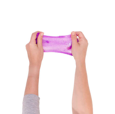 Hands holding bright pink slime. Playing with slime popular self made toy.