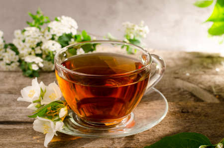 Tasty fragrant tea with jasmine flower. Glass tea cup on a old wooden table. Hot drink with flowers of philadelphus.