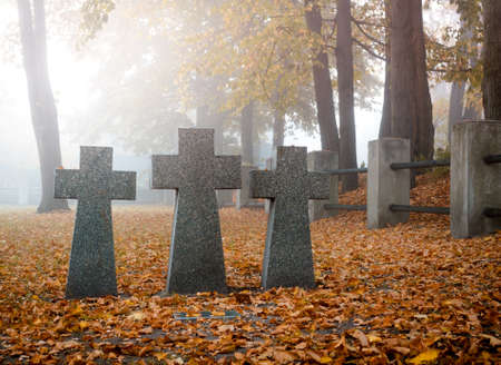 Grey granite crosses on a german soldier tomb. Graves of unknown soldiers on military cemetery in Kyiv, Ukraine. Autumnal morning scene Stock Photo