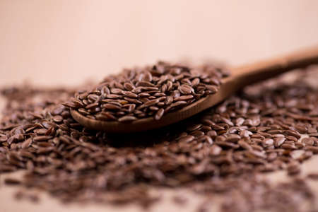 Close up Flax seeds in a wooden spoon. Organic Healthy food background.