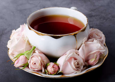 Romantic Tea time backdrop with vintage white porcelain tea cup, gentle pink roses on a dark gray background.