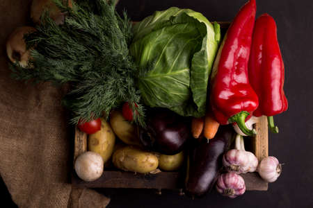 Assortment of fresh raw vegetables in a wooden box against black background. Healthy organic local food. Zdjęcie Seryjne
