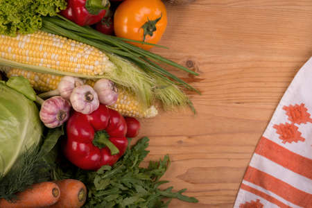 Assortment of fresh raw vegetables on a wooden table. Healthy organic local food. Top view background with empty space.