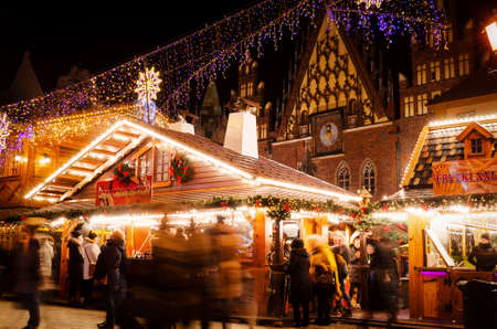Wroclaw, Poland - 11/25/2019: Traditional Christmas Pyramid on the Festive Market of Rynek Square against Historic old town hall. Long lasting exposure.